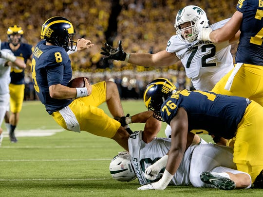 Michigan State's Kenney Willekes, bottom, sacks Michigan's