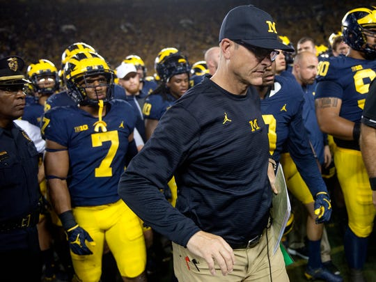 Michigan's coach Jim Harbaugh and the team head off