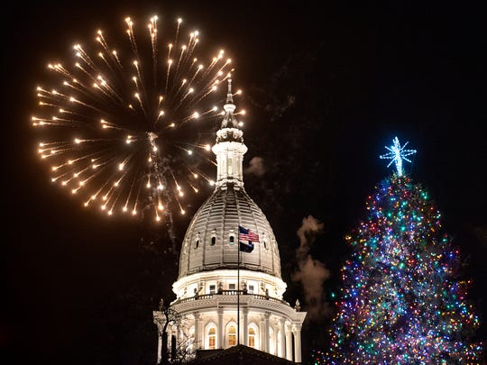 Fireworks explode over the Capitol and the lit Christmas