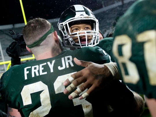 Michigan State senior Gerald Holmes, right, hugs fellow