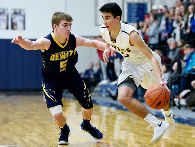 Haslett's Mitchell Mowid, right, looks for room as