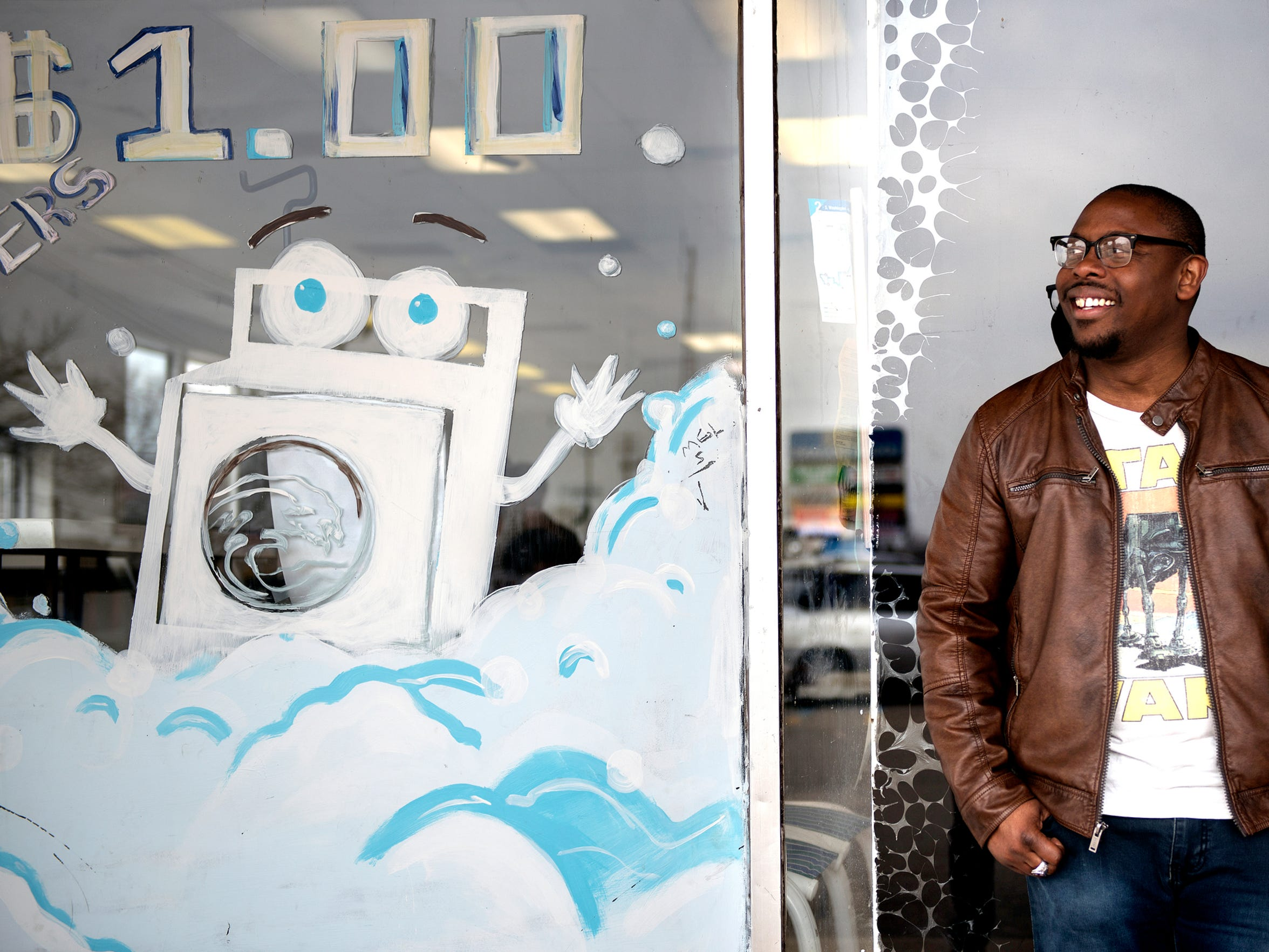 Ryan Holmes, 34, is an artist who grew up in Delta Township and lives in south Lansing. He recently painted a mural at the All Washed Up laundromat at 3222 S. Martin Luther King Blvd.