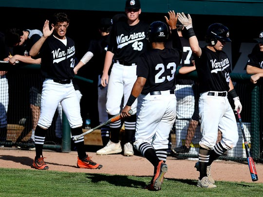 Birmingham Brother Rice's Gabe Sotres, center, celebrates his run with teammates during the third inning on Thursday, June 14, 2018, at McLane Stadium on the MSU campus in East Lansing.