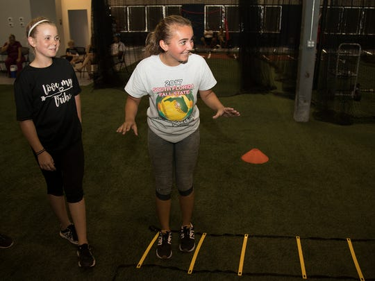 Kaylee Lambert, 12, left, and Sammi Rosado, 12, train on Wednesday at Cape Coral Indoor Athletics. The facility opened this month and features multi-sport performance training, summer camps, batting cages and speed and conditioning classes.