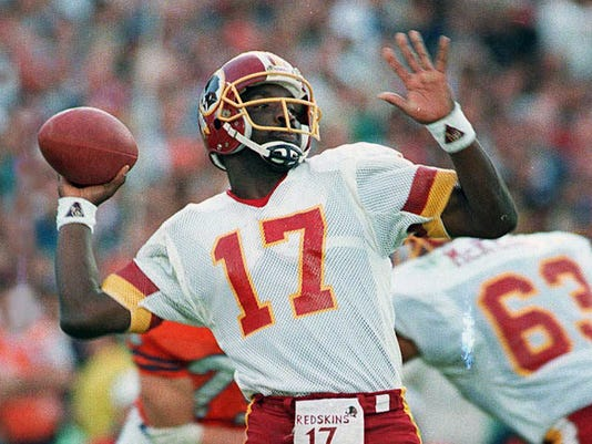FILE - In this Jan. 31, 1988, file photo, Washington Redskins quarterback Doug Williams prepares to let go of a pass during first quarter of Super Bowl XXII against the Denver Broncos in San Diego. Williams, who set a record with 340 yards passing in the NFL football game and became the first African-American quarterback to win a Super Bowl. (AP Photo/Elise Amendola, File)