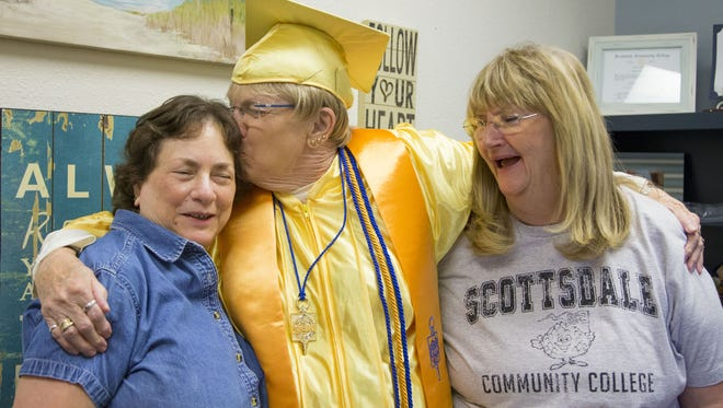 Former Scottsdale Community College adviser Fonda Christopher (left) and current Scottsdale Community College adviser Barb Ross (right) get hugs and kisses from Gwendolyn Carlson, 84, on her graduation day. Carlson is the oldest person to have ever graduated from Scottsdale Community College.