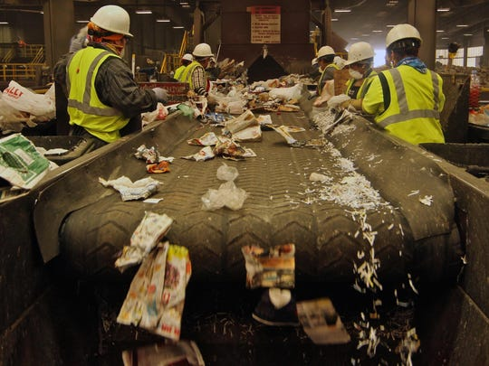 Workers pull out materials that should not have been put in a recycling bin at a Material Recovery Facility in Fontana in 2015.