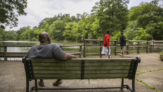 Clifton community members enjoy the view of the lake at Burnet Woods in June. The 90-acre park attracts members of the community for its walking trails and fishing.