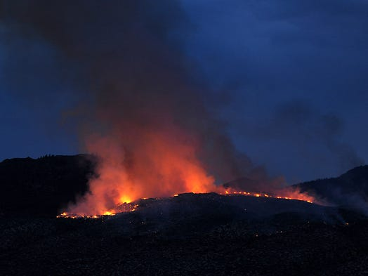 A wildland fire burns about 150 acres above U.S. 395 and south of US. 50 Wednesday night July 16, 2014.  There were at least 100 firefighters battling the blaze along with two helicopters and two tankers.