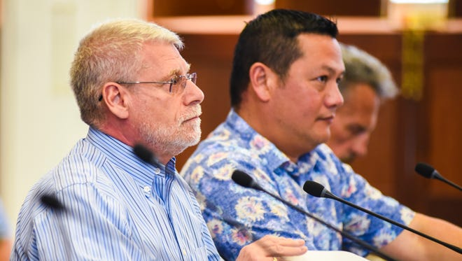 Edward Birn, left, Department of Administration acting director, listens to remarks by Sen. Joe S. San Agustin, Committee on Education, Finance and Taxation chairman, during a public hearing at the Guam Legislature in Hagåtña on Thursday, Mar. 8, 2018.