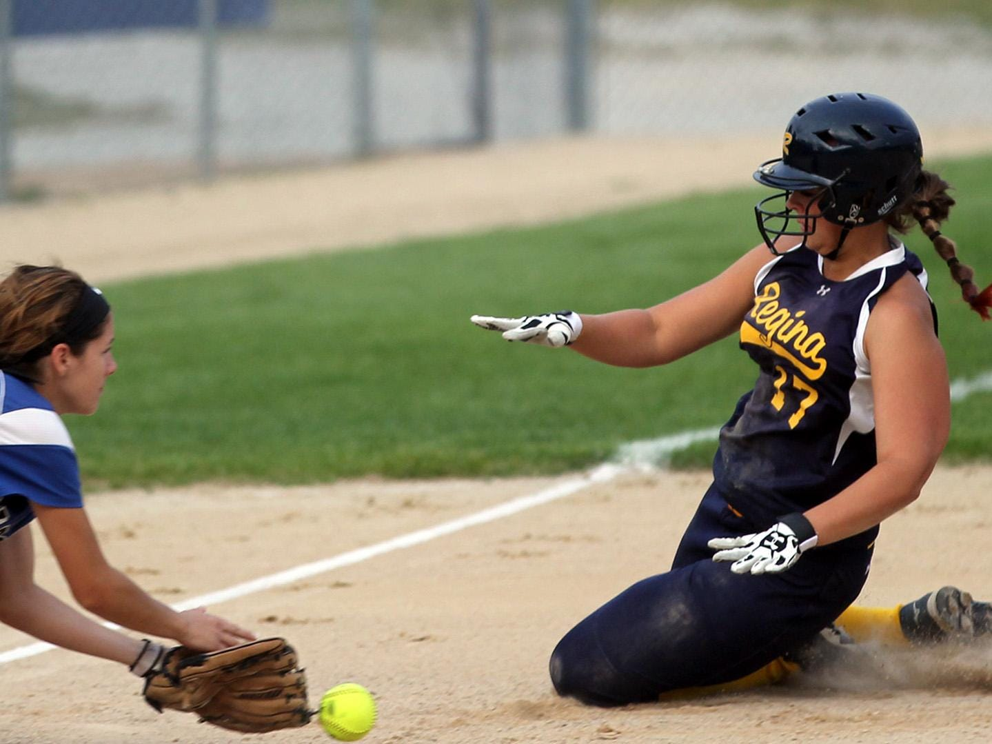 Regina's Hannah Stein safely slides to third base during the Regals' game against Columbus on Wednesday, July 8, 2015. David Scrivner / Iowa City Press-Citizen