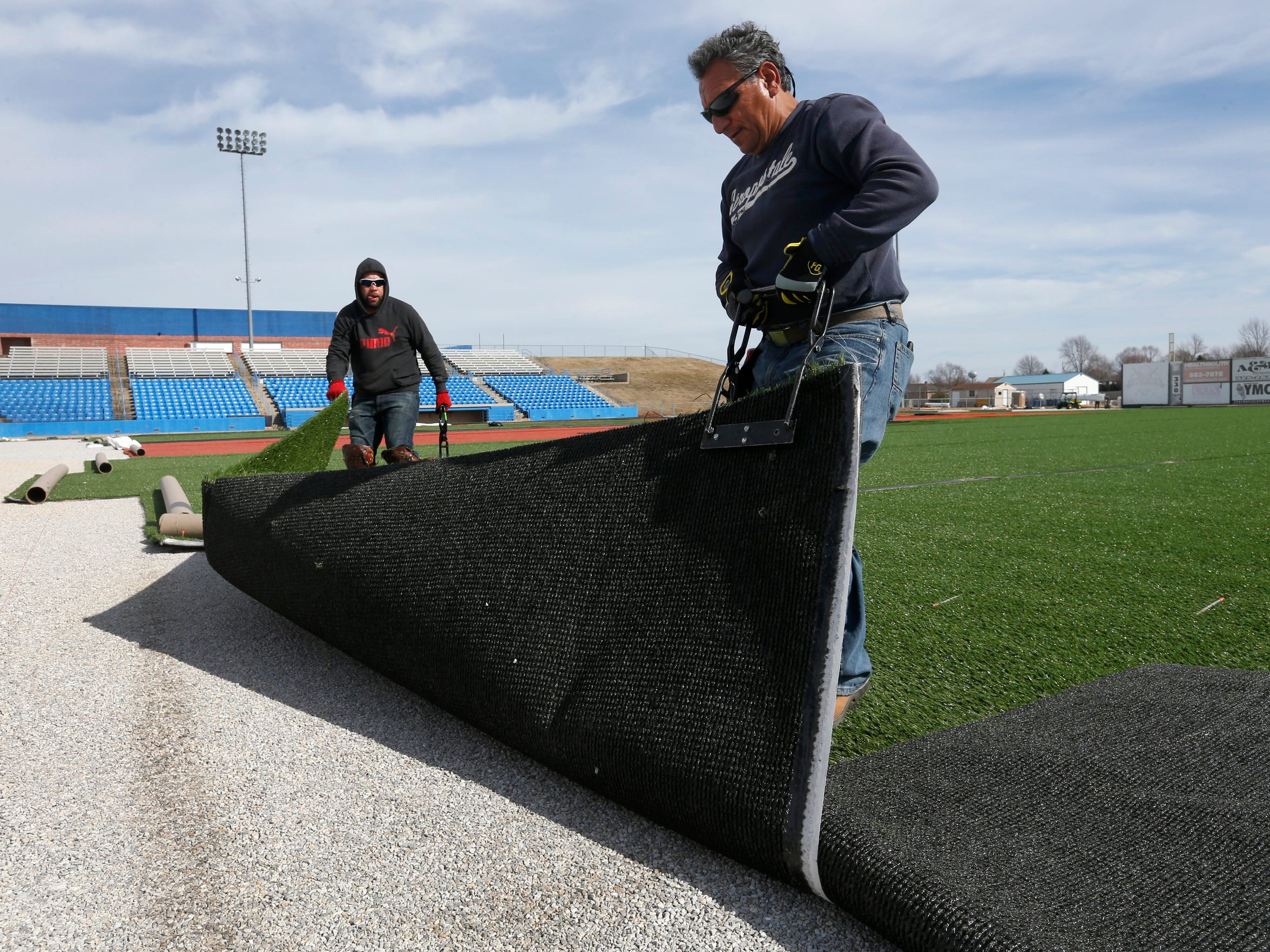 Juan Mariscal, right, and Juan Valdiva, both of Sports Construction Management, lift the edges of artificial turf to make room for a new section while installing the new field at Duck's Stadium in Ozark on Thursday, Feb. 18, 2016.