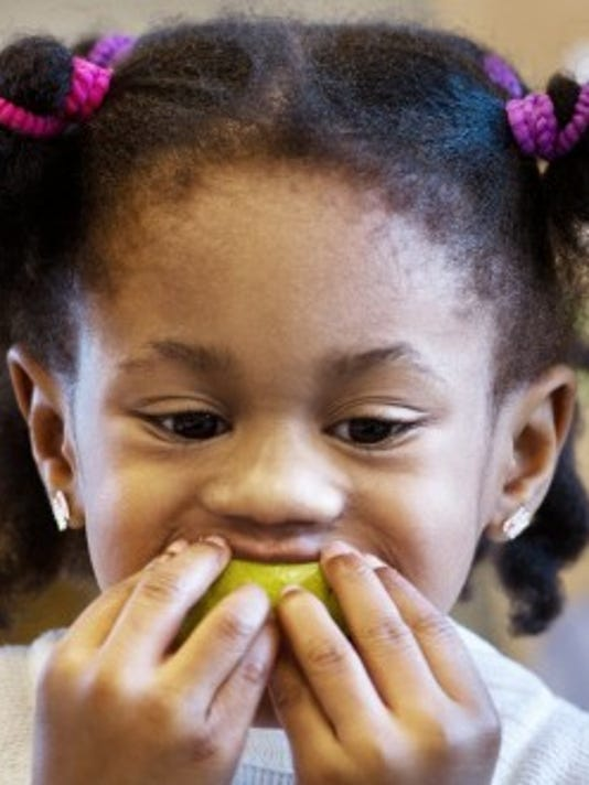 Arielle Fallon, 4, bites into a pear in March at the Keystone Kids Early Learning Center in Shrewsbury.  (Daily Record/Sunday News -- Paul Kuehnel)