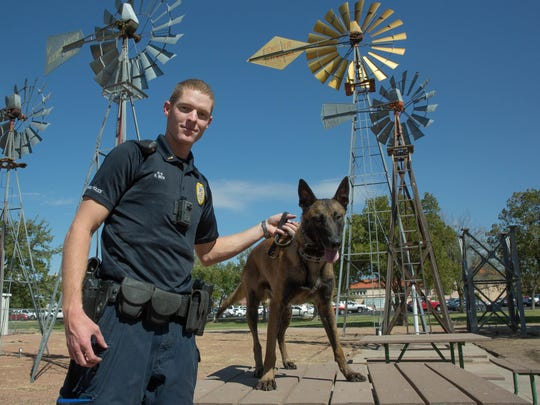 Sgt. Ryan Beck and Jackx, his Belgian Malinois partner, hang out near the New Mexico State Police Department Thursday October 12, 2017.