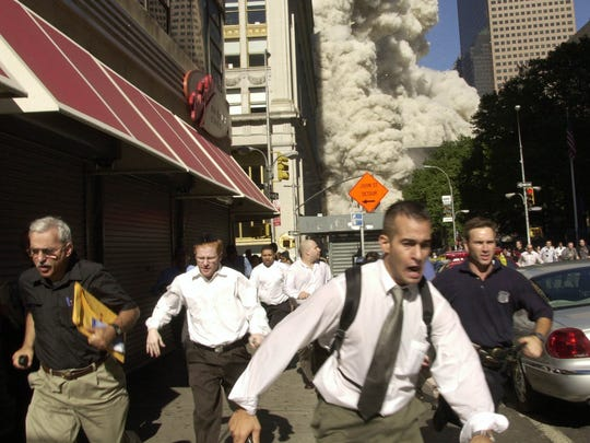 People run from the collapse of one of the twin towers