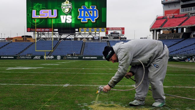 Terry Porch paints logos on the field Monday for the 2014 Franklin American Mortgage Music City Bowl.