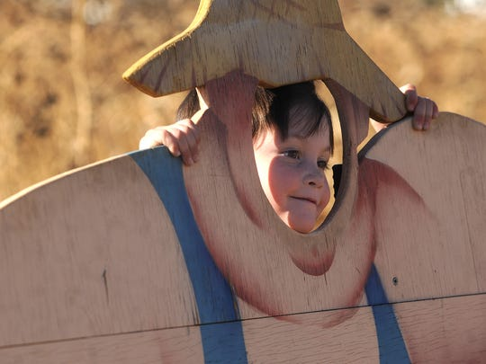 Asher Avila, 3, peeks through a cutout on Sunday, Oct. 21, 2012, at Something from the Farm in Fort Collins.