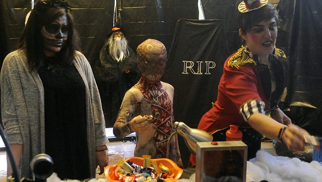 (From left) Raeanne Webb, Kindred Robinson, 10, Monica Robinson hand out candy at the Spooktacular.