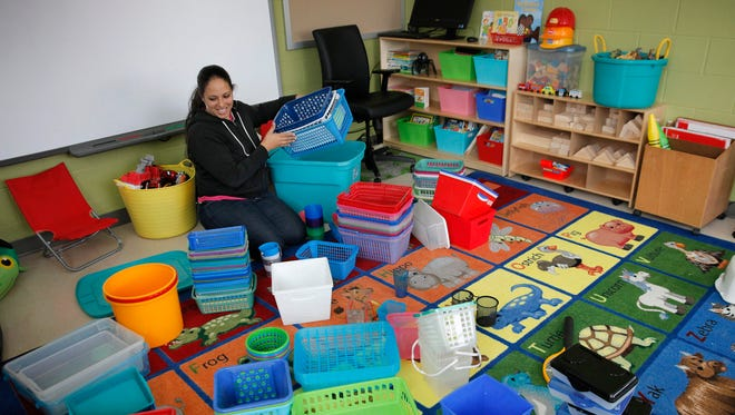 Kindergarten teacher Cristie Thornton organizes her room in the new addition to the World of Inquiry School.