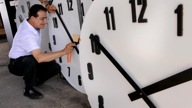 Sam Medawar works on repaired clock tower faces at his workshop in Lansing Tuesday July 21, 2015. The clock faces were remounted in the Haslett Commerce Center tower.