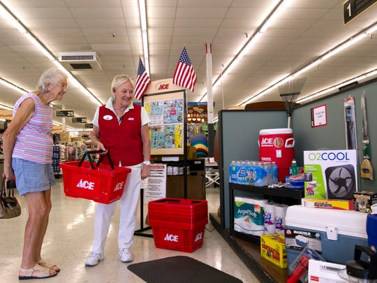Sunshine ACE hardware employee Julie Cook, right, speaks to customer Mary Denardis about the hurricane tax-free items.