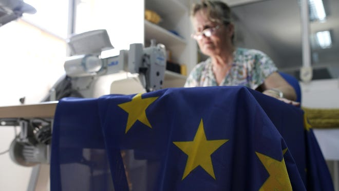 A seamstress sews an EU flag in a workshop in Belgrade, Serbia. Serbia, Montenegro, Macedonia, Bosnia, Kosovo and Albania, all at different stages in joining the EU, have declared that the British exit in a referendum last week will not diminish their membership efforts.