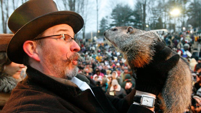 Punxsutawney Phil, right, is held by Ben Hughes after emerging from his burrow on Gobblers Knob in Punxsutawney, Pa., on Feb. 2, 2010.
