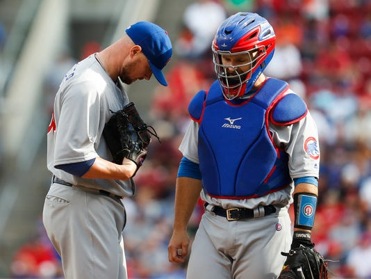 Chicago Cubs starting pitcher Jon Lester, left, meets with catcher David Ross, right, in the second inning of a baseball game against the Cincinnati Reds, Saturday, Oct. 1, 2016, in Cincinnati. (AP Photo/John Minchillo)