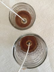 Pour a thin layer of wax into the bottom of your jars and place the wicks in the jars.