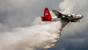 Tanker 05, a Lockheed P-2 Neptune fire tanker, makes a water drop at a farewell open house at the company's Missoula, Mont., headquarters on Oct. 1, 2017. The airplane was retired from Neptune's fleet after 24 years.