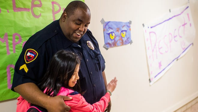Lafayette Police Department Corporal Jarvis Mayfield hugs student Tuyet Ho, 11, in the hallway at Paul Breaux Middle School in Lafayette, La., Friday, Nov. 20, 2015.