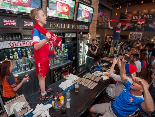 MacKale Crimmins, 11, of Washington Township stands on the bar to lead a cheer for the U.S. team at the Red Fox English Pub in Royal Oak. The rooftop pub will close this year to become Pinky's.