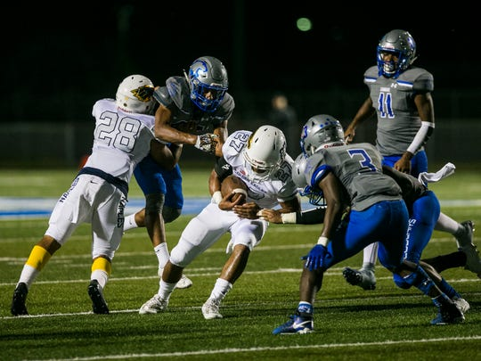 """Naples junior running back Cesare """"Chez"""" Mellusi is brought down by Barron Collier on Friday, Oct. 27, 2017. Naples won with a final score of 16-15 at Barron Collier High School."""