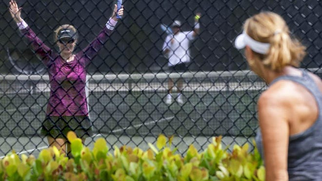 Nora and Sean Conlin, Wellington, (on court) wave to Kris Krigbaum, West Palm Beach, as they see each other for the first time since the coronavirus outbreak. The Wellington Tennis Center reopened for singles play on Wednesday.