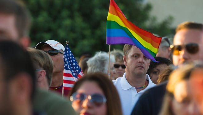 People gather to support the victims of Sunday's mass shooting at an Orlando gay nightclub outside Phoenix Pride on June 12, 2016 in downtown Phoenix, Ariz.