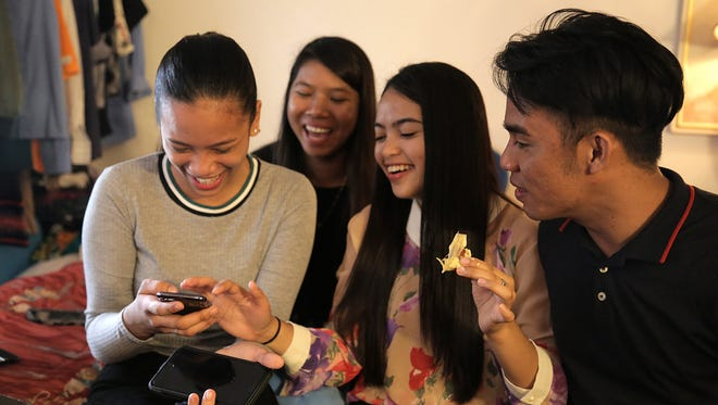 From left, Daisy Ray Bueno, 19; Honey Mae Canoy, 21; Honeylyn Cortez, 20; and Ogenloyd Silva, 26; share a laugh while checking social media in their room at the Time Zone Motel in Reno. All four took part in a work exchange program in the summer of 2017.