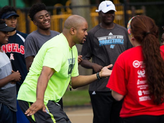 Former Portland Trailblazer, Desmond Ferguson, leads a group of young players in warmup exercises for the Spirit of Reaching Higher Levels Basketball Clinic at Claude Evans Park on Friday afternoon.