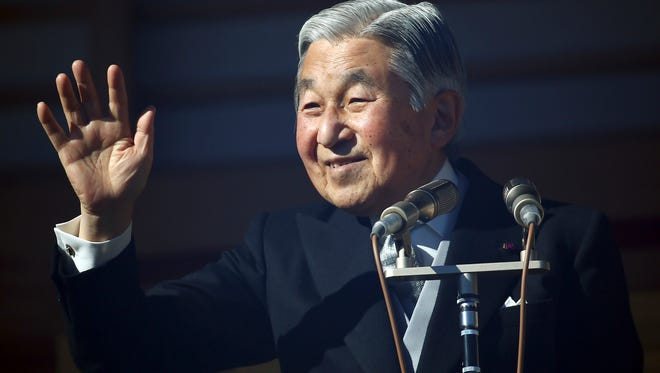 In this Dec. 23, 2014 file photo,  Japan's Emperor Akihito waves to well-wishers as he and family members appear on the balcony of the Imperial Palace during the emperor's 81th birthday in Tokyo.