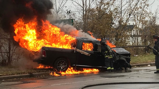 A black Dodge Ram pickup truck catches fire after crashing south of 8th and Locust streets on Wednesday, Nov. 15. The driver, Oleksiy Raldukhin, faces multiple felony charges.