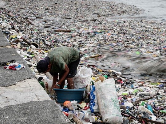 A man looks for salvageable materials among trash washed up on shore in Manila Bay after a tropical storm.