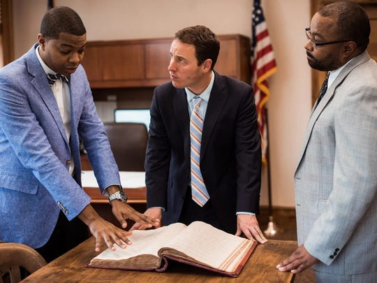 Deputy Register of Deeds Chris Beavers points to historic property records from the 1800s showing the transfer of slaves. Register of Deeds Drew Reisinger and Deputy Register of Deeds Keith Green look on. An initiative to digitize the records in Buncombe is leading to expansions statewide.