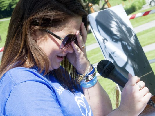 Alyssa Fiorentino breaks down in tears as she attempts to read a poem about her sister, Brooke, seen in a photograph in the background, during a heroin awareness vigil at William Kain Park on Saturday. Brooke died at age 26 from a heroin overdose earlier this year.