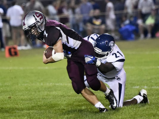 Shippensburg's Cole Friese (7) is brought down by Joshua Honorat (21) of Chambersburg on Friday night during the Greyhounds' 26-21 victory.