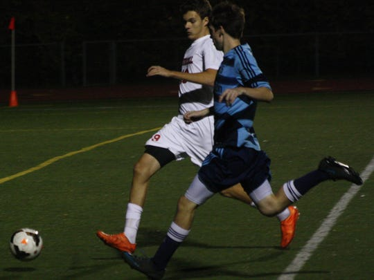 A Churchill defender runs step-for-step with Stevenson's Ryan Theisen Monday night.