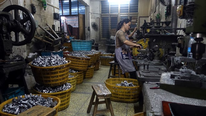 A worker manufactures metal parts in an auto parts factory in Rui'an near Wenzhou city in eastern China's Zhejiang province. Chinese exporters of goods from electronics to motorcycle parts are scrambling to insulate themselves from U.S. President Donald Trump's proposed tariff hike. They are weighing plans to rush shipments to American customers ahead of the increase, raise prices or find other markets. Some are looking at shipping goods through other countries to hide their Chinese origin.