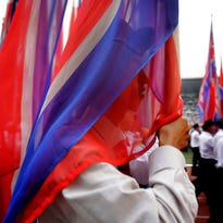 """Men carry the national flag of North Korea during the """"Pyongyang Mass Rally on the Day of the Struggle Against the U.S.,"""" attended by approximately 100,000 North Koreans to mark the 65th anniversary of the outbreak of the Korean War at the Kim Il Sung stadium, Thursday, June 25, 2015, in Pyongyang, North Korea. The month of June in North Korea is known as the """"Struggle Against U.S. Imperialism Month"""" and it's a time for North Koreans to swarm to war museums, mobilize for gatherings denouncing the evils of the United States and join in a general, nationwide whipping up of the anti-American sentiment."""