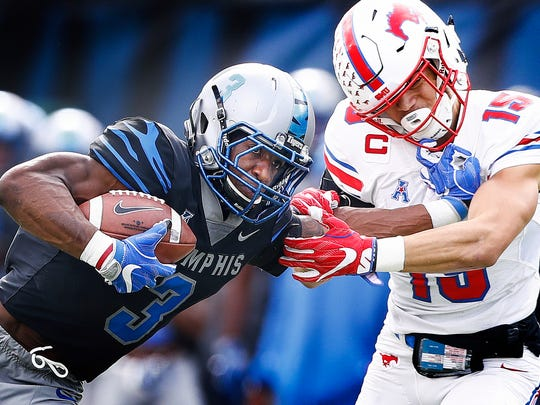 Memphis receiver Anthony Miller (left) stiff arms SMU defender Jordan Wyatt (right) while scrambling for a first down during first quarter action in Memphis, Tenn., Saturday, November 18, 2017.
