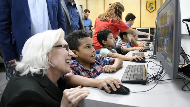 California Senator Jean Fuller watches as Jayden Miles, 7, plays a game in the new computer lab at the Boys & Girls Club of Exeter.