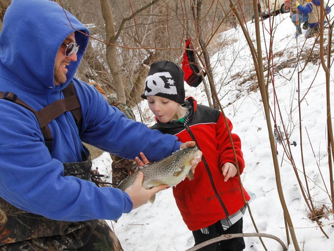 PJ Pringle of Greece proudly shows off the 3-pound brown trout he just landed to his son, PJ Pringle Jr., 6, as the two fish on the opening day of trout season at Powder Mills Park in Pittsford on April 1, 2014.   Anglers turned out in force for the 11th annual John Riedman Foundation Opening Day Trout Derby at the park, which helps support operations at the park's historic fish hatchery.