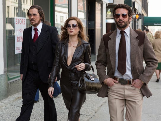 """This photo released by Sony Pictures shows Christian Bale, left, as Irving Rosenfeld, Amy Adams as Sydney Prosser, and Bradley Cooper as Richie Dimaso walking down Lexington Avenue in a scene from Columbia Pictures' film, """"American Hustle.""""  The film was nominated for a Golden Globe for best motion picture, musical or comedy on Thursday, Dec. 12, 2013.  The 71st annual Golden Globes will air on  Sunday, Jan. 12. (AP Photo/Sony - Columbia Pictures, François Duhamel)"""
